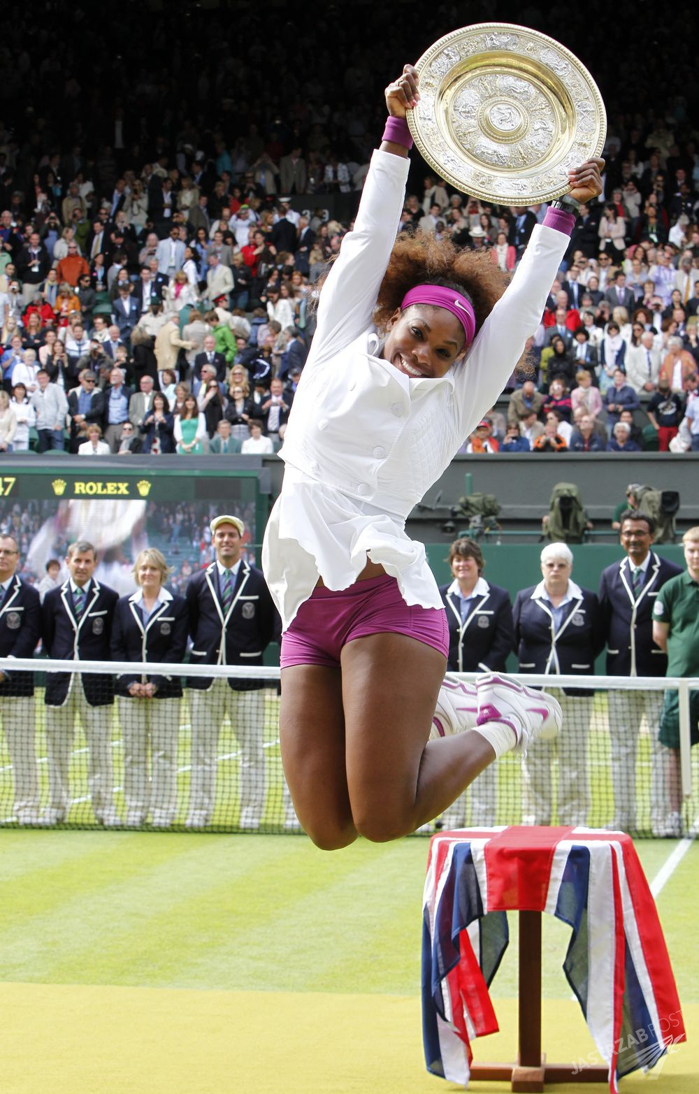 (120707) -- LONDON, July 7, 2012() -- Serena Williams of the United States jumps with the trophy in her hands in the awarding ceremony after defeating Agnieszka Radwanska of Poland in the women's final tennis match at the Wimbledon tennis championships in London July 7, 2012.   (/Wang Lili)