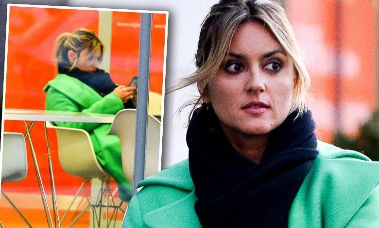 Karolina Szostak w zielonym płaszczyku w banku