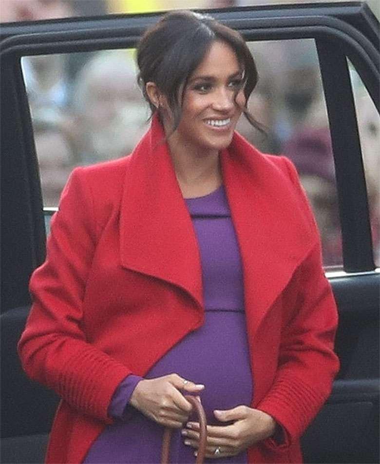 Meghan Markle z ciążowym brzuszkiem w czerwonym płaszczu