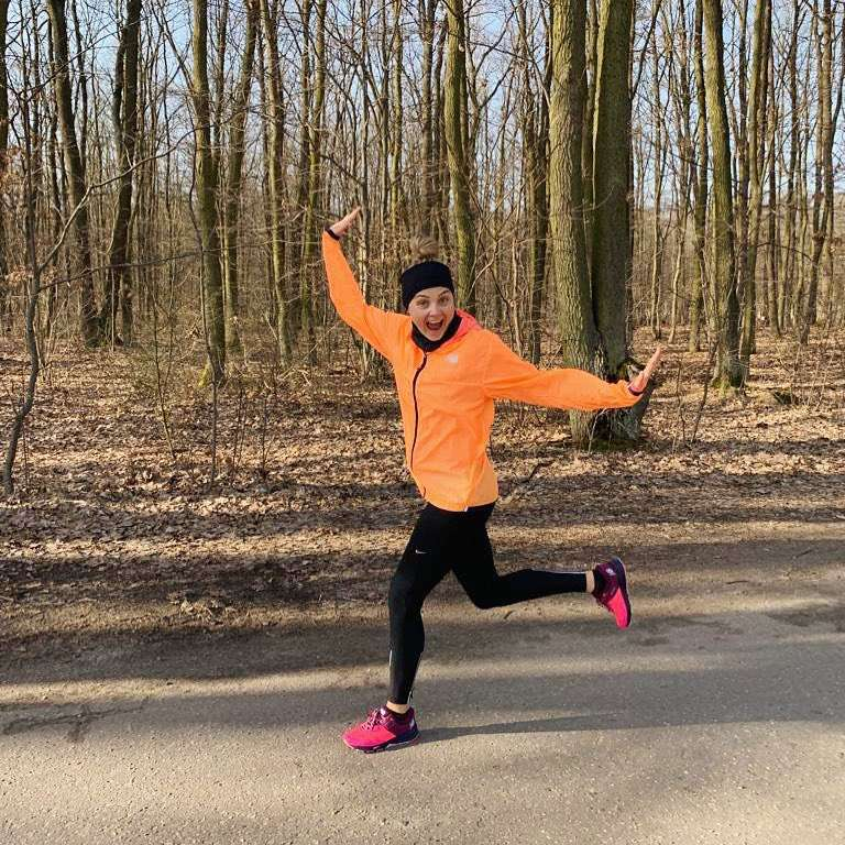 Małgorzata Socha w stylowych dresach biega po lesie