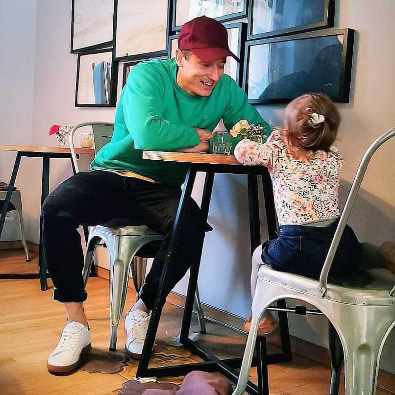 Robert Lewandowski siedzi z córeczką Klarą przy stoliku