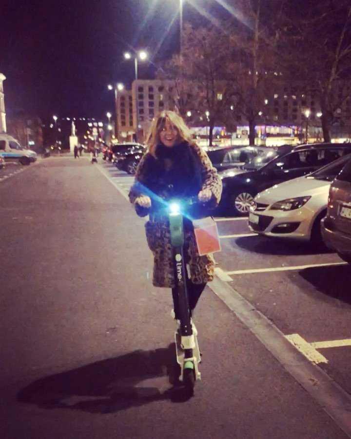Karolina Szostak z torbą faworków jedzie na hulajnodze